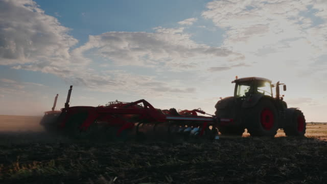Tractor harrows the field at sunset. Steadicam shot video