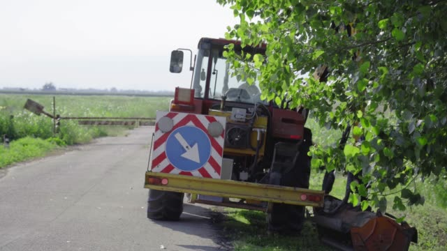 Tractor in the countryside with arm brush cutter Tractor in the countryside with arm brush cutter alongside and road sign with arrow agricultural occupation stock videos & royalty-free footage