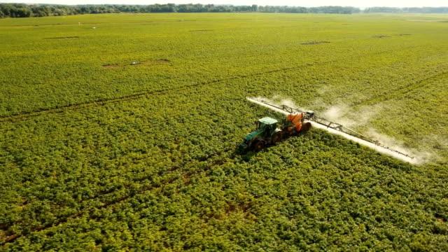 vídeos de stock e filmes b-roll de tractor is spraying fertilizers field - pulverizar