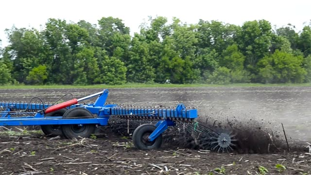 Tractor plow land. Tractor with double wheeled ditcher digging drainage canal. Harrow Mattock Rotational. harrow agricultural equipment stock videos & royalty-free footage