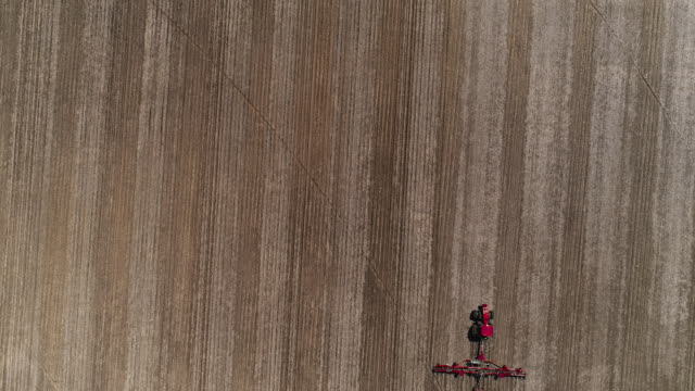 Tractor plowing and fertilizing the agricultural fields in the springtime nearby Lyndon Township, Illinois, USA. Aerial drone accelerated video with the forward and tilting-up camera motion.