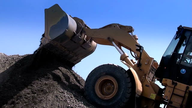 Tractor pours rubble from the ladle. Tractor pours rubble from the ladle. Heavy construction equipment. Construction equipment at work. Bulldozers are gaining a scoop rubble. Building. construction equipment stock videos & royalty-free footage