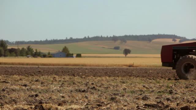 Tractor pulling plow across dusty field