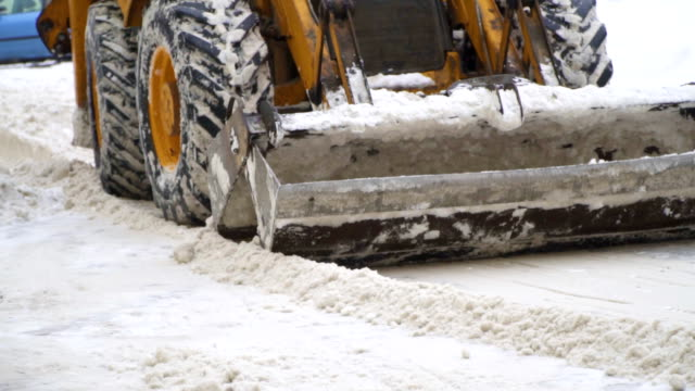 Tractor shoveling snow on the street. Slow-motion. Tractor shoveling snow on the street. Slow-motion. construction vehicle stock videos & royalty-free footage