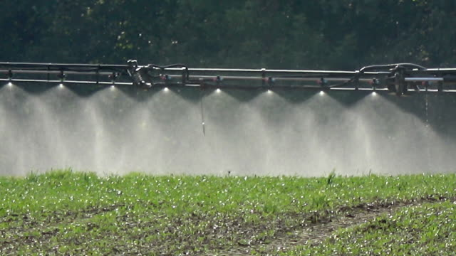 Tractor spraying agriculture field, machinery detail video