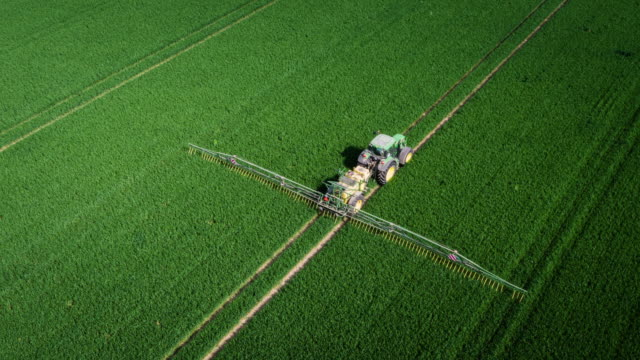 AERIAL: Tractor spraying chemicals video