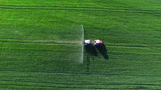 tractor spraying crop field in spring flyover - trattore video stock e b–roll