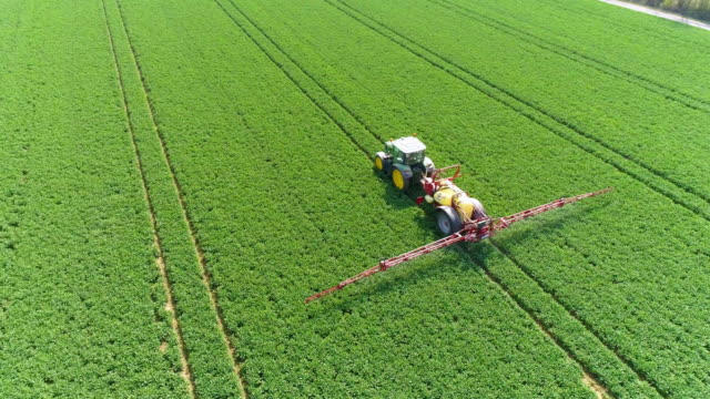 tractor spraying crop in spring flyover - insetticida video stock e b–roll