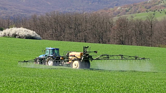 Tractor spraying field, rural landscape in countryside video