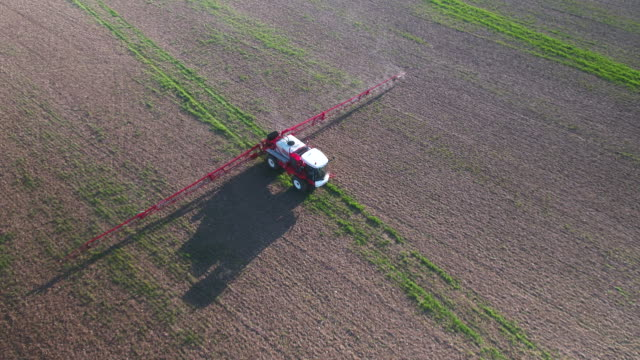 tractor spraying fields on an arable farm with glyphosate herbicide - insetticida video stock e b–roll