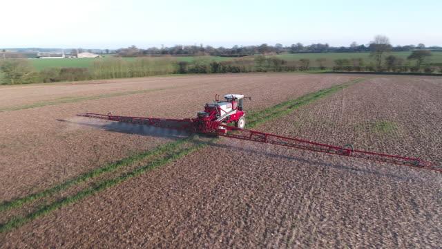 vidéos et rushes de tracteur pulvérisation des champs arables dans une ferme avec le glyphosate herbicide - herbicide