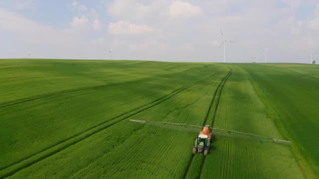 hava traktör üttürme böcek böceklerini rüzgar türbinleri ile çevrili bir alana püskürttü - gıda ve i̇çecek sanayi stok videoları ve detay görüntü çekimi