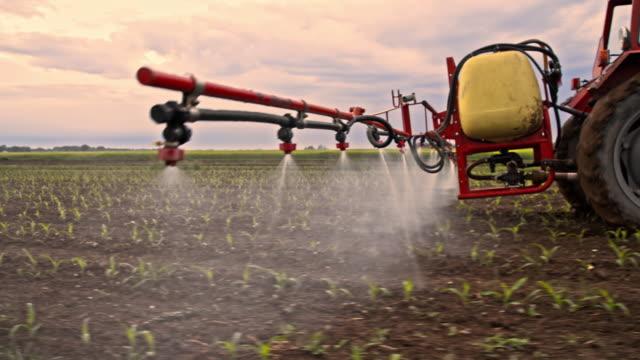 vídeos de stock e filmes b-roll de trator pulverização de pesticidas em um campo - pulverizar