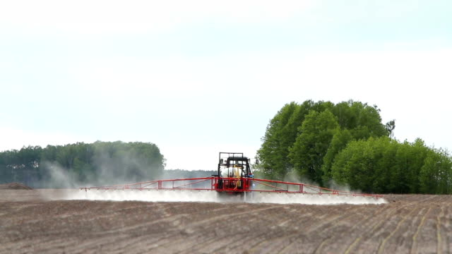 tractor sprays a field with chemical fertilizers for agriculture video
