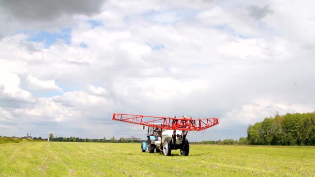 vidéos et rushes de tracteur arrose un champ avec des engrais chimiques pour l'agriculture - herbicide