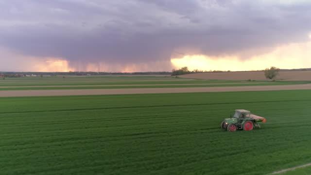 antenna trattore che diffonde fertilizzante su un campo - fertilizzante video stock e b–roll