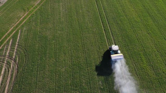 concimi di spandimento trattore su campo colturali primaverili, aerei - fertilizzante video stock e b–roll