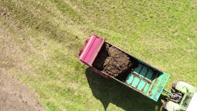 aerial trattore che diffonde letame sull'hrass - fertilizzante video stock e b–roll