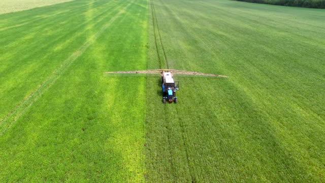 vidéos et rushes de champ de haricots sprinkles tracteur - herbicide