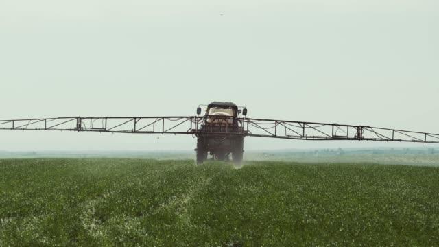 vidéos et rushes de tracteur avec un pulvérisateur de travaux dans le domaine. - herbicide
