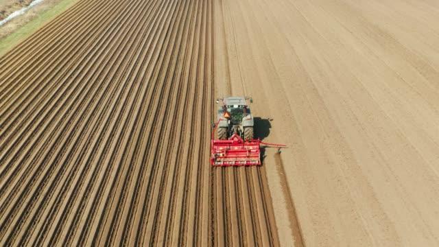 vídeos de stock e filmes b-roll de tractor with disc harrows on the farmland - terra cultivada