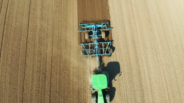 Tractor with disc harrows on the farmland aerial view farm tractor with rotary harrow plow preparing land for sowing. Tractor with harrows prepares the agricultural land for planting crop. Cultivation of farmland by disc harrows. harrow agricultural equipment stock videos & royalty-free footage