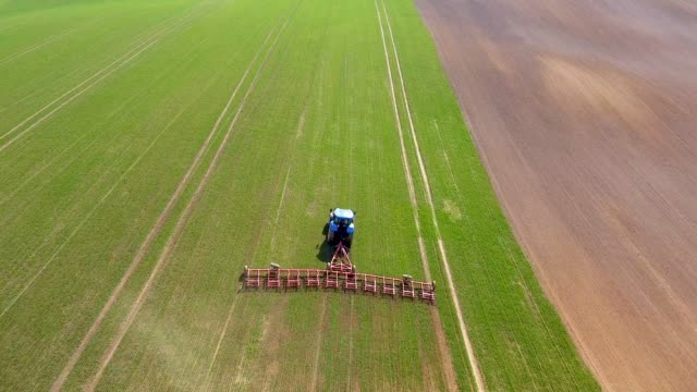 Tractor with harrows prepares the agricultural land for planting crop Drone fields series harrow agricultural equipment stock videos & royalty-free footage