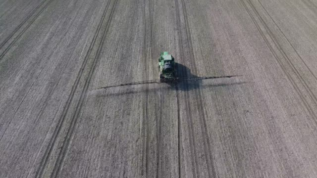 tractor with hinged system of spraying pesticides. fertilizing with a tractor - fertilizzante video stock e b–roll
