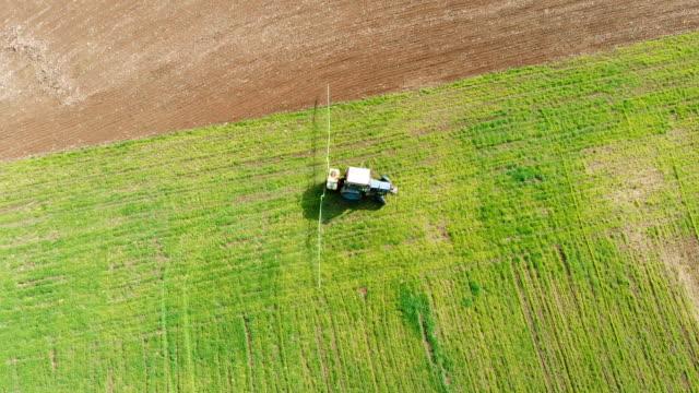 Traktor med monterad spruta för att göra herbicider utspelar sig på tur tillbaka på kanten av fältet med korn video