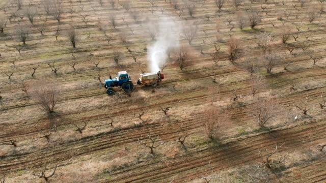Traktor med särskild enhet sprutar bekämpnings medel på träd i frukt odling video