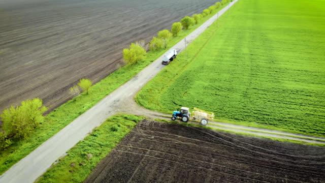 Traktor med spruta drar upp till last bil med tank av giftiga kemikalier för behandlings fält video