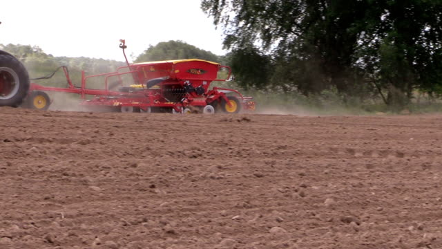 Tractor working in field. Time of sowing. Planting crops. video