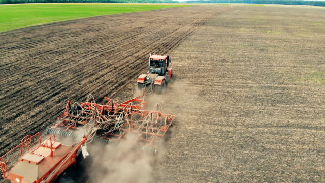 A tractor works on a big field, cultivating ground. 4K. Aerial.