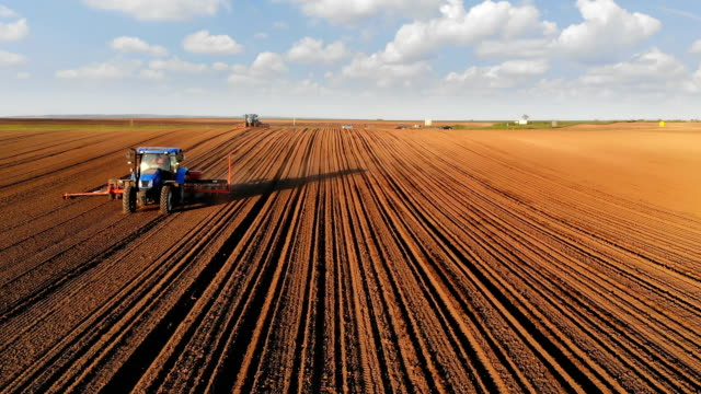 Tractors planting crops Aerial view of a farmers in two tractors seeding. Drone shot of sowing agricultural crops at field sowing stock videos & royalty-free footage