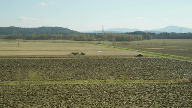 AERIAL: Tractors working on a field in early spring video
