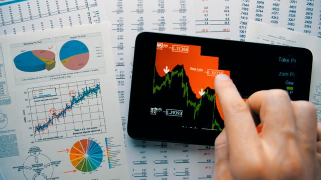 Trader moving graphics currency quotes on the screen of the tablet Trader moving graphics currency quotes on the screen of the tablet. Closeup. The camera is rotating financial occupation stock videos & royalty-free footage