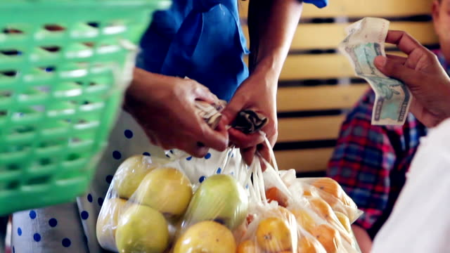 Trading on the market. Trading on the market. Buyer is calculated with the seller. Buying food. Buying food at the shop. myanmar stock videos & royalty-free footage