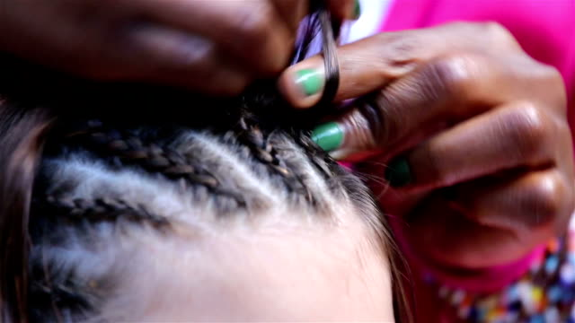 Traditional African braids. Woman braids hair girl on the street. video