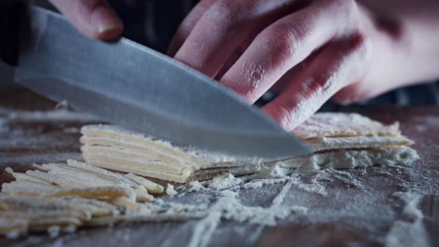 4k traditionelle bäcker schneiden teig in hausgemachte pasta - selbstgemacht stock-videos und b-roll-filmmaterial