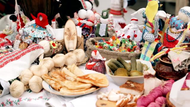 traditional belarusian cuisine - pancakes. attribute of traditional folk celebration of eastern slavic national traditional holiday maslenitsa. winter spring holiday. belarusian folk dolls - славянская культура стоковые видео и кадры b-roll