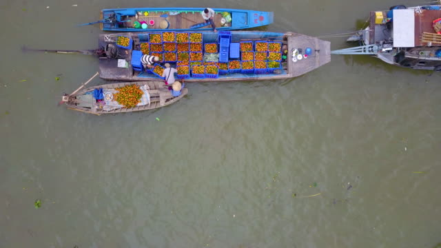 Traditional Cai Rang floating market Aerial view, top view Cai Rang floating market. Tourists, people buy and sell food, vegetable, fruits on the boat, ship at river market. A traditional popular method of buying and selling on river market homegrown produce stock videos & royalty-free footage