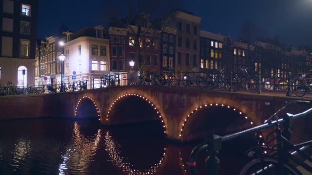 Traditional canal bridge, old dancing houses or buildings and empty street in Amsterdam at night, Netherlands video