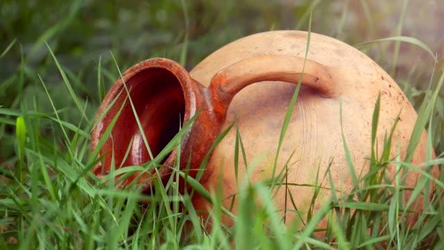 vidéos et rushes de jug en céramique traditionnel se trouvant dans l'herbe close-up - picto urne