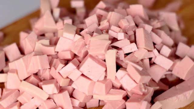 i tradizionali cubi da taglio chiamati mortadela ruotano su tavola di legno. preparazione per insalata - mortadella video stock e b–roll