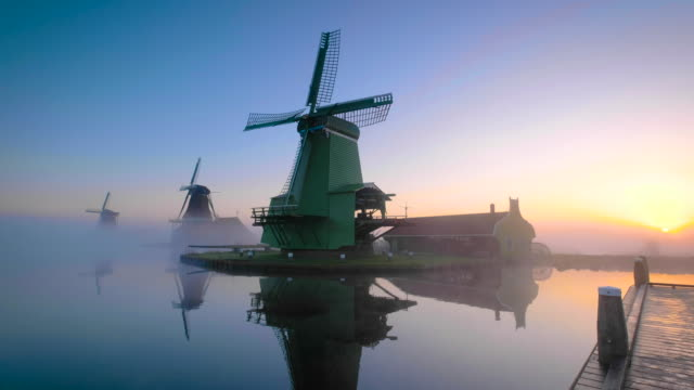 Traditional Dutch windmills in the mist during sunrise along a canal at the Zaanse Schans in The Netherlands