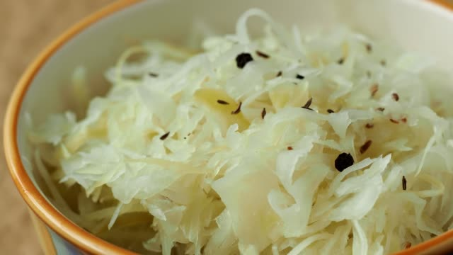 Traditional fermented cabbage sauerkraut in the bowl Fermented cabbage. Bowl of sauerkraut (pickled white cabbage) cabbage stock videos & royalty-free footage