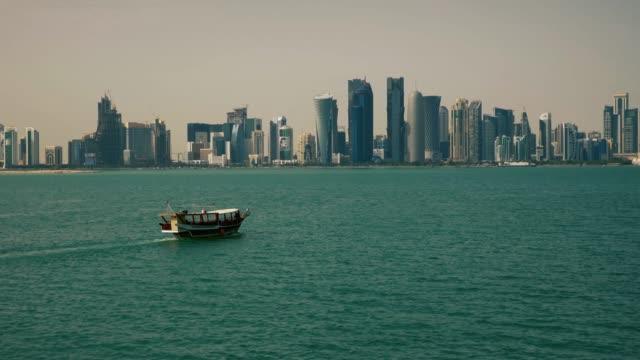 vidéos et rushes de bateau de pêche traditionnel passant près des gratte-ciels à doha qatar moyen-orient - doha