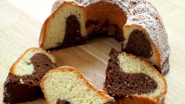 stockvideo's en b-roll-footage met traditionele zelfgemaakte marmeren cake. marmeren bundt cake gesneden op houten tafel - marmer