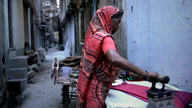 Traditional Indian Lady ironing clothes in a narrow lane video