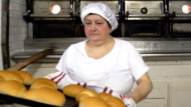 vidéos et rushes de boulangeries italiennes traditionnelles. la femme prend le boulanger sortir les brioches du four - boulanger
